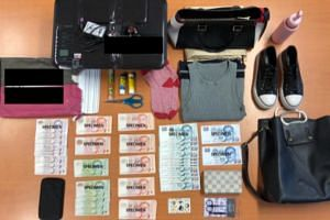 The police seized several items from the woman, including two $50 notes which are believed to be counterfeits, a printer, printing paper, stationery and $1,200.