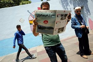 "An Iranian reading the Sazandegi newspaper with a picture of a US drone and headline in Persian reading ""Defence from Iran border"" in Teheran last Saturday. Tensions in the Middle East may play a part in market developments this week. PHOTO: EPA-EFE"