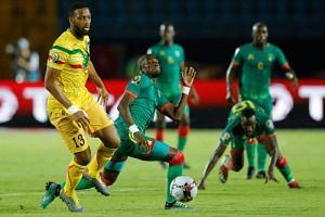 Mali's defender Molla Wague (left) vies for the ball during the Africa Cup of Nations match against Mauritania  in Suez, Egypt, on June 24, 2019.