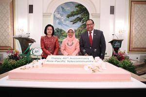 (From left) Secretary-general of the Asia-Pacific Telecommunity Areewan Haorangsi, President Halimah Yacob and Communications and Information Minister S Iswaran at the cake-cutting ceremony celebrating the 40th anniversary of the Asia-Pacific Telecom