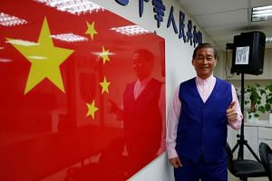 Chang An-lo, leader of the Chinese Unification Promotion Party, poses next to a Chinese national flag in Taiwan, on May 2, 2019.