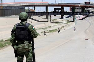 A member of the Mexican National Guard observes migrants running to cross illegally into the US.