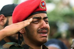An unidentified son of deceased Major-General Gezayi Abera salutes his father's flag-draped coffin during the funeral ceremony.