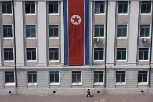 A pedestrian walks past a North Korean flag displayed on a building in Pyongyang, on April 12, 2019.