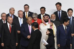 US President Donald Trump greets Chinese President Xi Jinping as other world leaders look on during the G-20 summit in Osaka, Japan, on June 28, 2019.