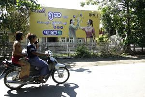 Two Rakhine women ride a motorcycle past a telecommunications advertisement poster in Sittwe.