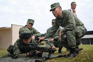 Army Safety Inspectorate's Inspection Team 1 Leader Major Simon Chew (right) inspecting a soldier as SAF Inspector-General Brigadier-General Tan Chee Wee (behind, left) looks on during a training inspection of 41SAR at Pasir Laba Camp on Feb 28, 2019