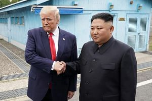 US President Donald Trump and North Korean leader Kim Jong Un shaking hands on the southern side of the Military Demarcation Line in Panmunjom on June 30, 2019.