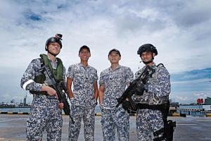 (From left) 3SG Lionel Loo, sea soldier, 3SG Ryan Ang, UAV operator, 3SG Marcus Ng, weapon system team member and CPL Vishesh Arora, Accompany Sea Security Team (ASSeT) member, at Tuas Naval Base.