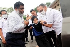Johor Health Director Dr Selahuddeen Abd Aziz (far left) helping a student of Sekolah Kebangsaan Kopok, Pasir Gudang, who was suffering from breathing difficulties and nausea yesterday.