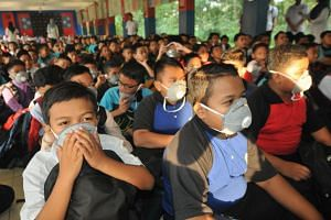 Students putting on masks at a school in Pasir Gudang, Johor. A total of 475 educational institutions in Pasir Gudang were closed for three days due to air pollution.