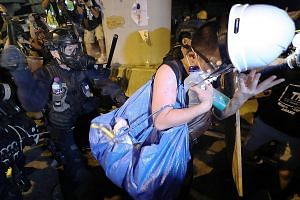 Riot police clashing with protesters as they moved to retake the Legislative Council building in Hong Kong early this morning. Hundreds of protesters had stormed the building yesterday on the 22nd anniversary of the city's handover from British rule