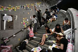 "People removing Post-it notes with messages about democracy and universal suffrage from the ""Lennon Wall"" at the Central Government Complex in Hong Kong yesterday. ST PHOTO: LIM YAOHUI"