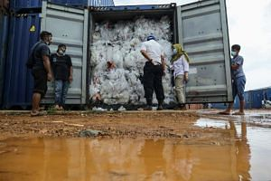 Indonesian officials check one of the 49 containers loaded with a combination of garbage, plastic waste and hazardous materials in violation of import rules, on Batam island on June 19, 2019.