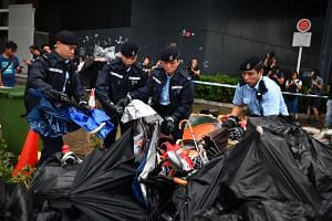 Police sort through items retrieved from inside the Legislative Council building, taking photographs as evidence, wrapping them up and loading some of them into a truck on July 3, 2019.