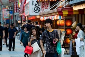 Pedestrians on a shopping street in Osaka. The Japanese government has scheduled an increase in the sales tax to 10 per cent from 8 per cent in October. Aware that the hike could hurt spending, Tokyo is pinning its hopes on mobile payments, an indust