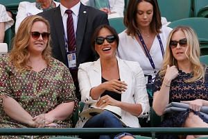 Meghan (centre) watches the match between Serena Williams and Slovenia's Kaja Juvan.