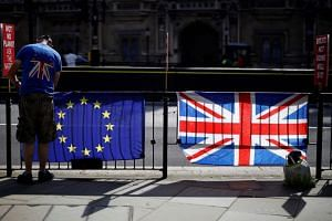An acctivist secures an EU flag to a railing opposite the Houses of Parliament in Westminster, central London on July 2, 2019.