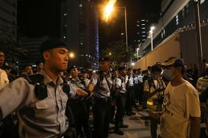 Policemen hold hands to line up and surround protesters during a demonstration in Tuen Mun.