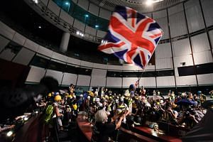 A protester waves the Union Jack flag inside the Legislative Council building during a demonstration against the Chinese government on July 1, 2019.
