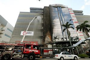SCDF officers putting out a fire that broke out on the facade of the building at 30 Toh Guan Road on May 4, 2017.