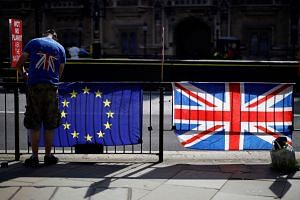 An anti-Brexit activist secures an EU flag to a railing opposite the Houses of Parliament in Westminster, central London, on July 2, 2019.