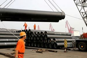 Workers directing a crane lifting steel pipes for export at a port in Lianyungang, Jiangsu province, China, on June 30, 2019.