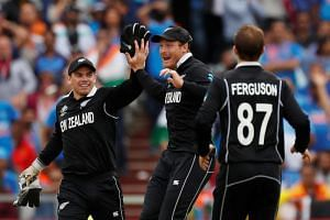 New Zealand's Martin Guptill celebrates with teammates after taking the wicket of India's MS Dhoni.