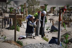 Two women decorate a grave in a Uighur graveyard on the outskirts of Hotan in China's north-west Xinjiang region.