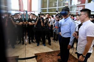 Education Minister Ong Ye Kung tries out a virtual reality project in Nanyang Polytechnic. He's guided by SkillsFuture Earn and Learn Programme student Brian Koh.