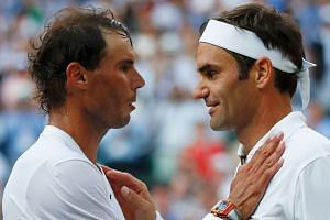 Switzerland's Roger Federer (right) shakes hands and embraces Spain's Rafael Nadal after Federer won their semi-final.