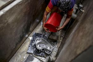 A worker cleans dustbin with medical surgical dishes outside an emergency ward at Sudar Hospital in Chennai, India, on July 4, 2019.