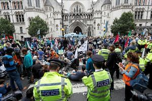Climate activists hold a protest outside the Royal Courts of Justice in London, Britain on July 15, 2019.