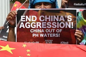 Activists display anti-China placards and flags during a protest at a park in Manila on June 18, 2019.