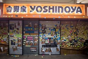 Protest notes cover the shuttered front of a Yoshinoya restaurant in the Shatin district of Hong Kong, on July 14, 2019.