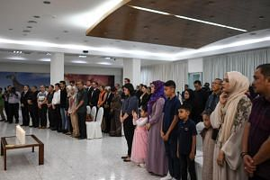 Relatives of passengers who perished aboard flight Malaysia Airlines flight MH17 observe a minute of silence during a commemoration ceremony at the Australian High Commission in Kuala Lumpur on July 17, 2019.