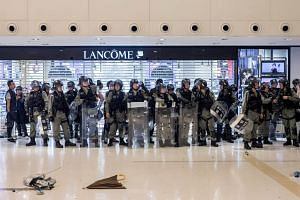 Riot police stand off against demonstrators inside New Town Plaza shopping mall during a protest in the Shatin district of Hong Kong, on July 14, 2019.