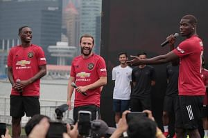 Manchester United players (from left) Aaron Wan-Bissaka, Juan Mata and Paul Pogba bantering on stage at the float at Marina Bay on July 21, 2019.