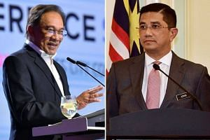 Malaysia's Economic Affairs Minister Azmin Ali (right) said he will work with PKR president Datuk Seri Anwar Ibrahim (left) who had extended an olive branch on July 20 at a retreat which the former and his allies did not attend.