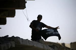 A member of the Iraqi security forces celebrates as he holds an Islamic State flag on top of a building destroyed in clashes in Mosul, Iraq, on July 10, 2017.