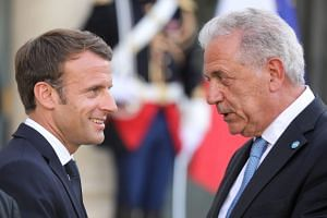 Macron (left) speaks with EU Commissioner for Migration, Home Affairs and Citizenship, Dimitris Avramopoulos, after their meeting in Paris.