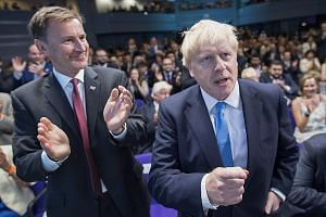 British Foreign Secretary Jeremy Hunt applauding as his rival for the Conservative Party leadership Boris Johnson clinched the vote yesterday. Mr Johnson will succeed Mrs Theresa May as British prime minister, taking over a country in crisis and a go