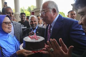 Former Malaysian prime minister Najib Razak blowing out the candle as he celebrated his 66th birthday with his supporters in the lobby of a court complex at the Kuala Lumpur High Court yesterday. Najib is facing several criminal proceedings over the