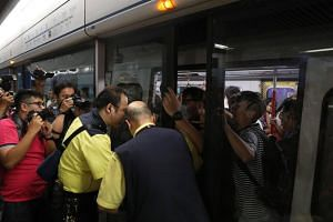 Protesters preventing the doors of a train from closing as MTR staff try to stop them at Admiralty station on July 24, 2019.
