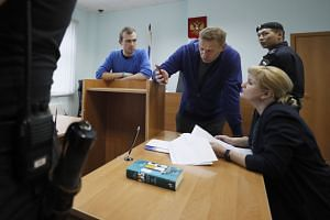 Navalny (centre) talks to his lawyer prior to a court session in Moscow.
