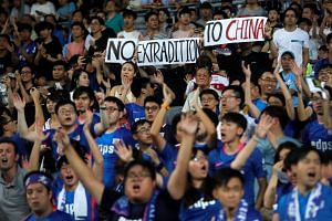 Fans hold an anti-extradition Bill banner during the Hong Kong friendly.