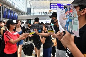 Protesters giving out pamphlets to passengers arriving at Hong Kong International Airport on July 26, 2019.