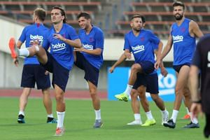 Barcelona forward Antoine Griezmann (second left) warming up during a training session with Barcelona in Kobe on July 25, 2019.