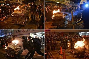 Protesters push a trolley with burning cardboard towards the police in Sheung Wan on July 28, 2019.