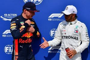 Hamilton shakes hands with Red Bull's Dutch driver Max Verstappen after the qualifying session.